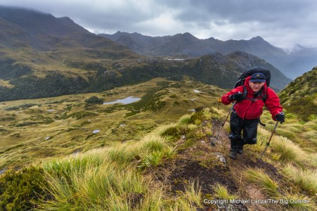 A backpacker in the rain on the Dusky Track in New Zealand's Fiordland National Park.