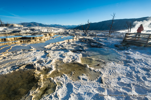 A hiker watching sunrise at Mammoth Hot Springs, Yellowstone National Park.