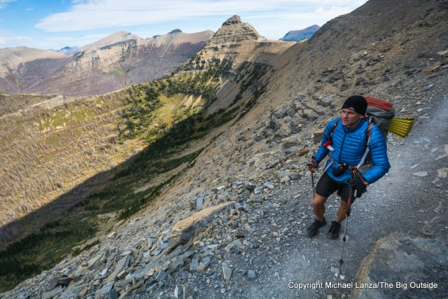 A backpacker on the windy trail from Pitamakan Pass to Dawson Pass in Glacier National Park.