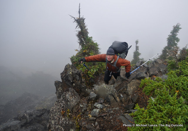A backpacker scrambling the Catwalk on a rainy, windy day in the Olympic Mountains.
