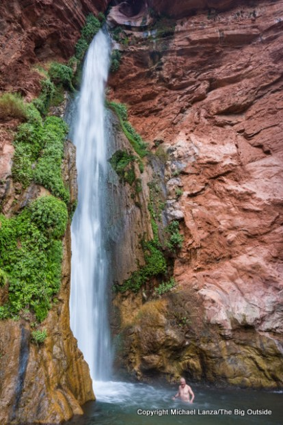 A hiker cooling off below Deer Creek Falls in the Grand Canyon.