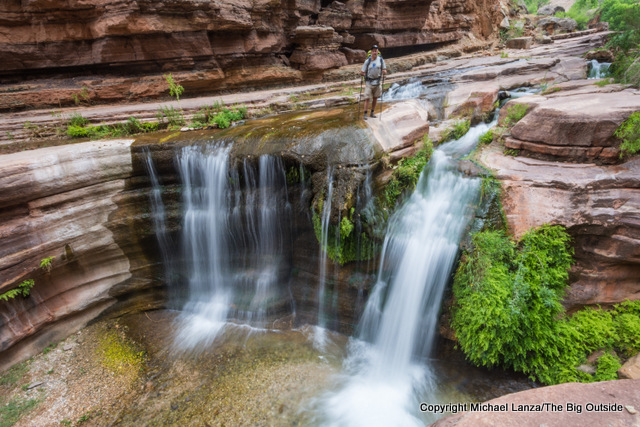A backpacker at a waterfall on The Patio, Deer Creek Trail, Grand Canyon.