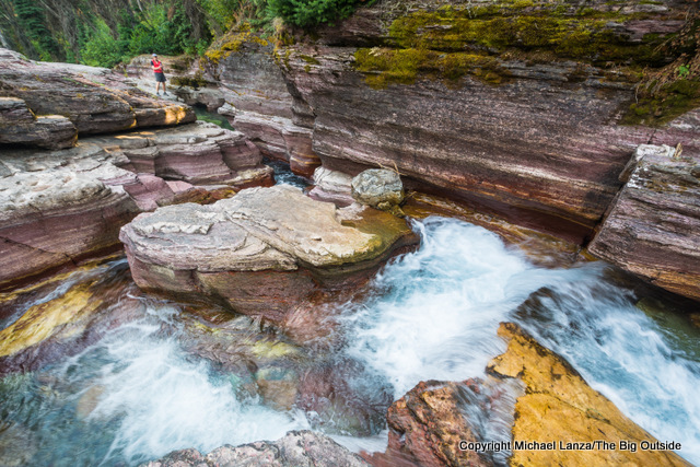 A backpacker at Deadwood Falls in Glacier National Park.