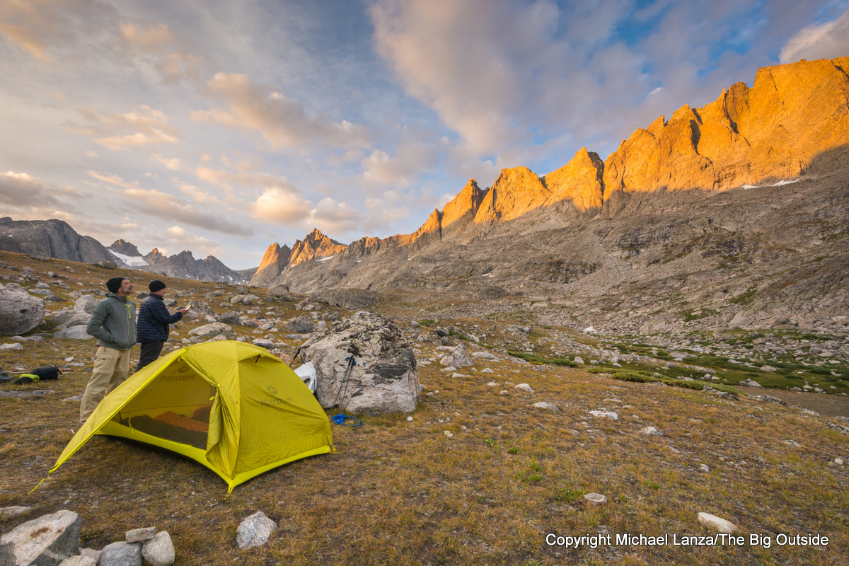 Backpackers watching sunset at a campsite in Titcomb Basin, Wind River Range, Wyoming.