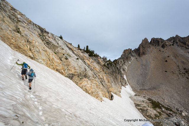 Hikers on steep snow off-trail in Idaho's Sawtooth Mountains.