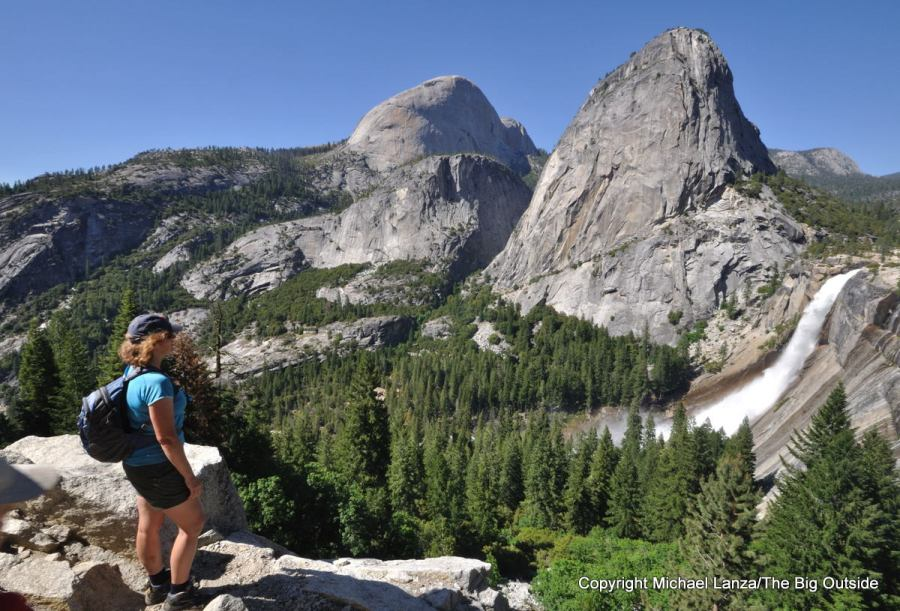 A hiker on the John Muir Trail in Yosemite overlooking Half Dome, Liberty Cap, and Nevada Fall.