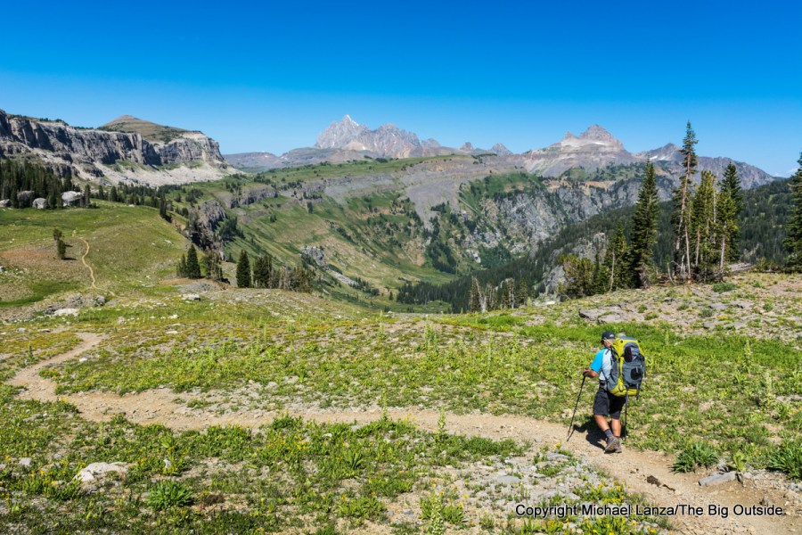 A backpacker hiking the Teton Crest Trail on Death Canyon Shelf, Grand Teton National Park.