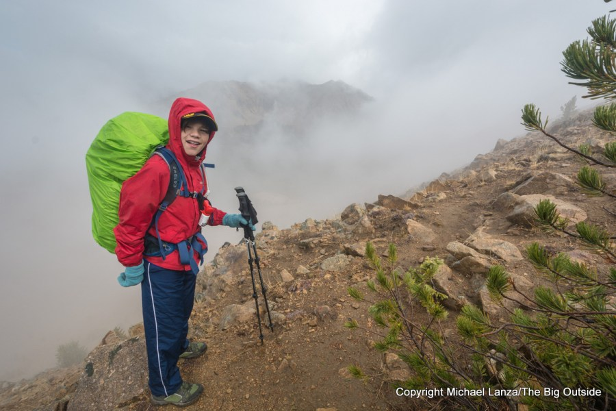 A teenage boy backpacking on a rainy day in Idaho's White Cloud Mountains.