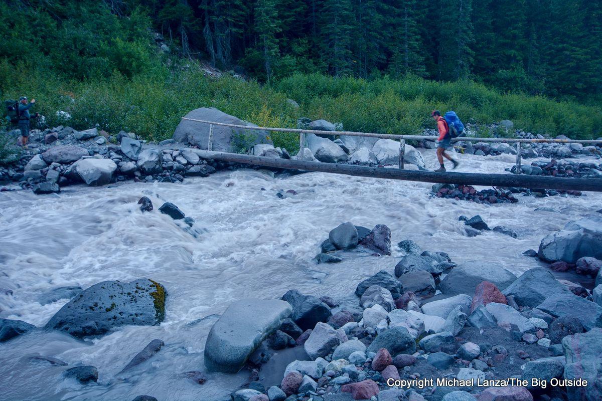 A backpacker crossing Winthrop Creek on the Wonderland Trail, Mount Rainier National Park.
