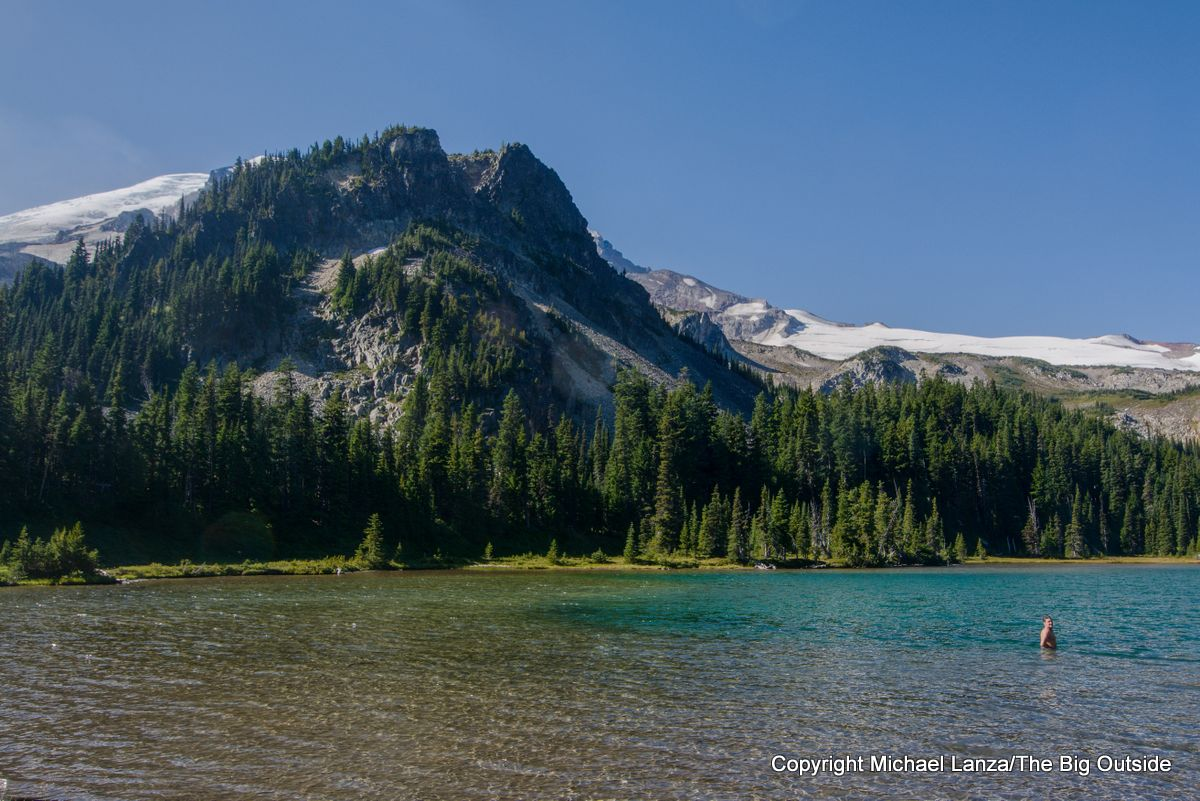 A backpacker swimming in Mystic Lake on the Wonderland Trail, Mount Rainier National Park.