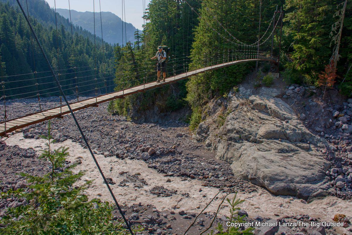 A backpacker crossing the Tahoma Creek suspension bridge on the Wonderland Trail, Mount Rainier National Park.