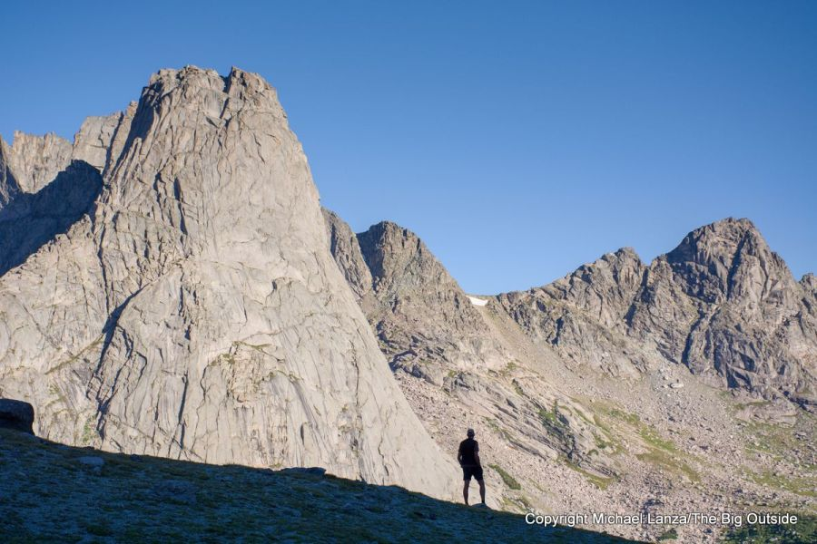 A backpacker below Jackass Pass, overlooking the Cirque of the Towers on the Wind River High Route, Wyoming.