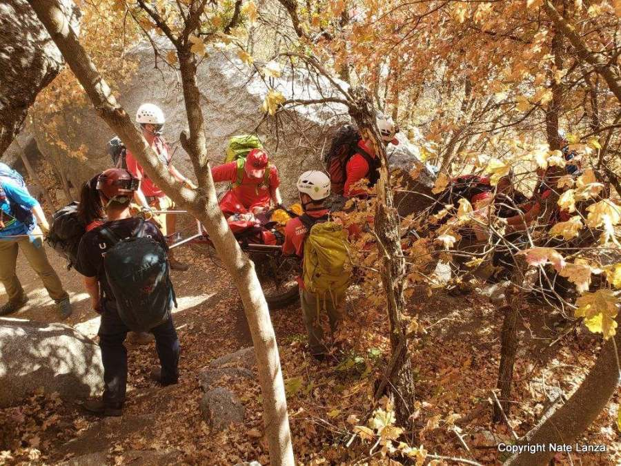 Rescuers evacuating a rock climber in a litter from Little Cottonwood Canyon.