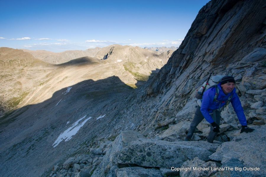 A backpacker scrambling up Europe Peak on the Wind River High Route.