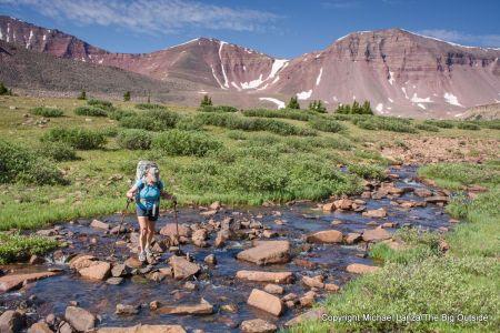 A backpacker hiking Uinta River Trail 44 in Painter Basin below 13,538-foot Kings Peak (right), High Uintas Wilderness, Utah.