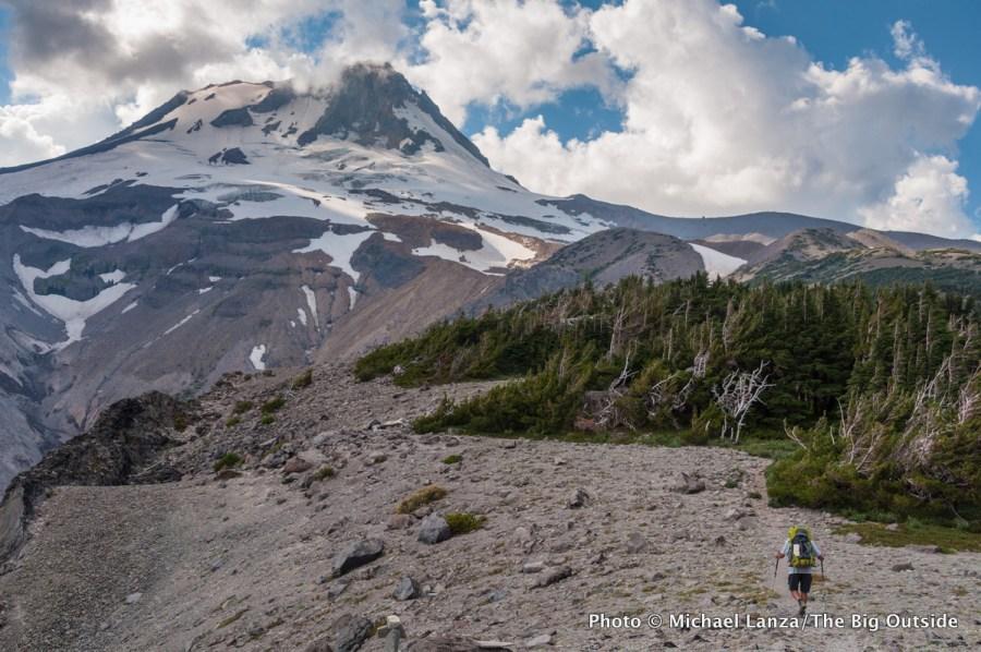 A backpacker hiking the Timberline Trail over Gnarl Ridge, Mount Hood, Oregon.