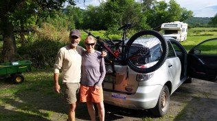 Rich and Chandra on the budding homestead with Chandra's new transportation behind her. (The bicycle not the car;-)!