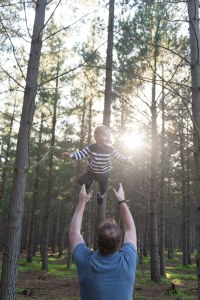 Dad throwing toddler in the air in forest