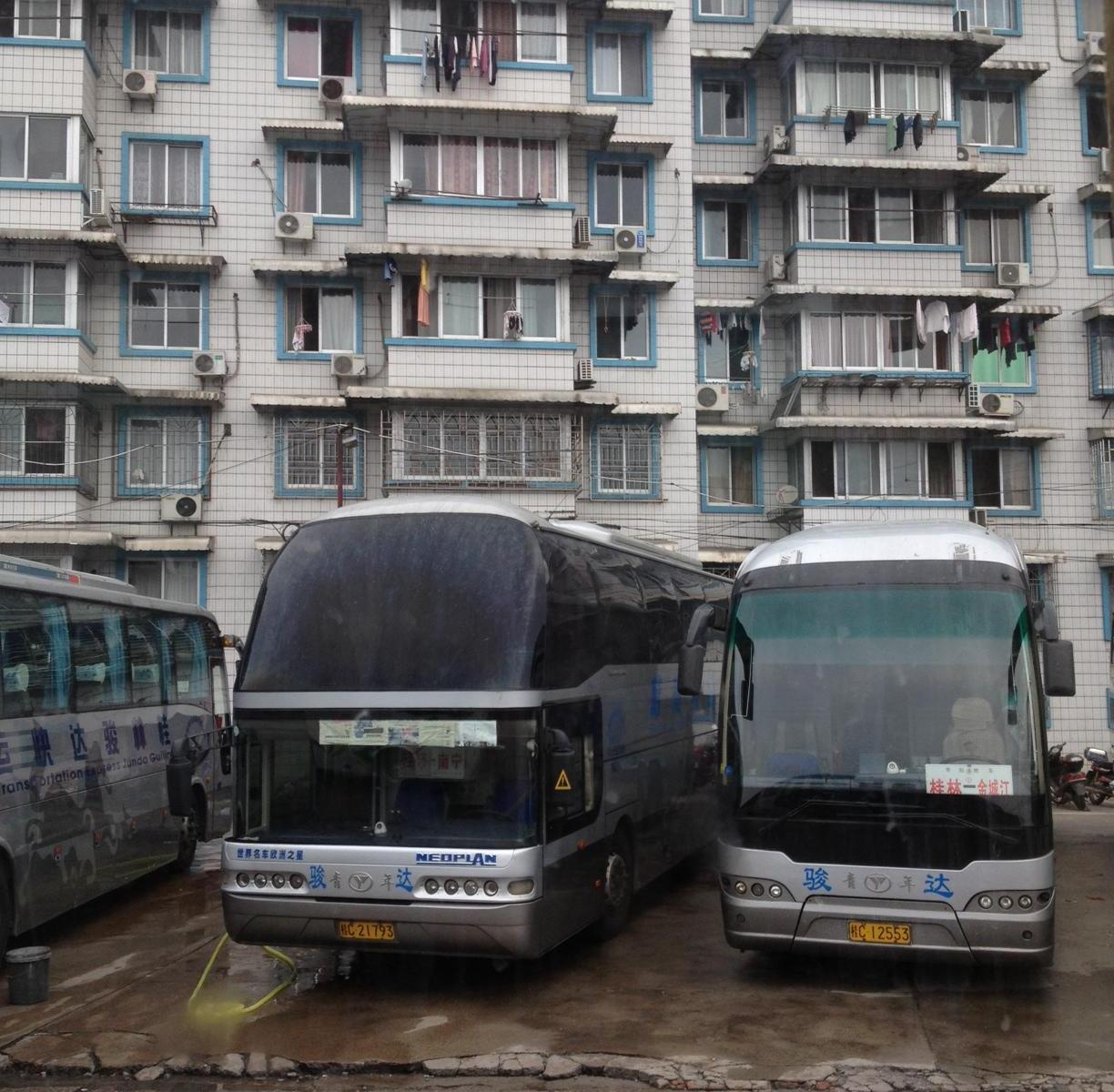 Coach buses parked in front of apartment buildings.