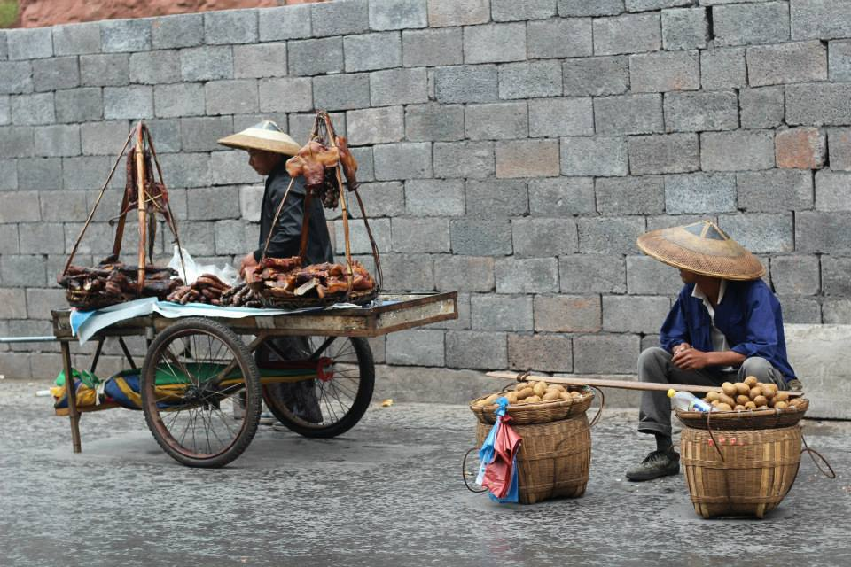Two street sellers with wicker hats. One has a cart of cured meat while the other has fresh produce in two large wicker baskets.