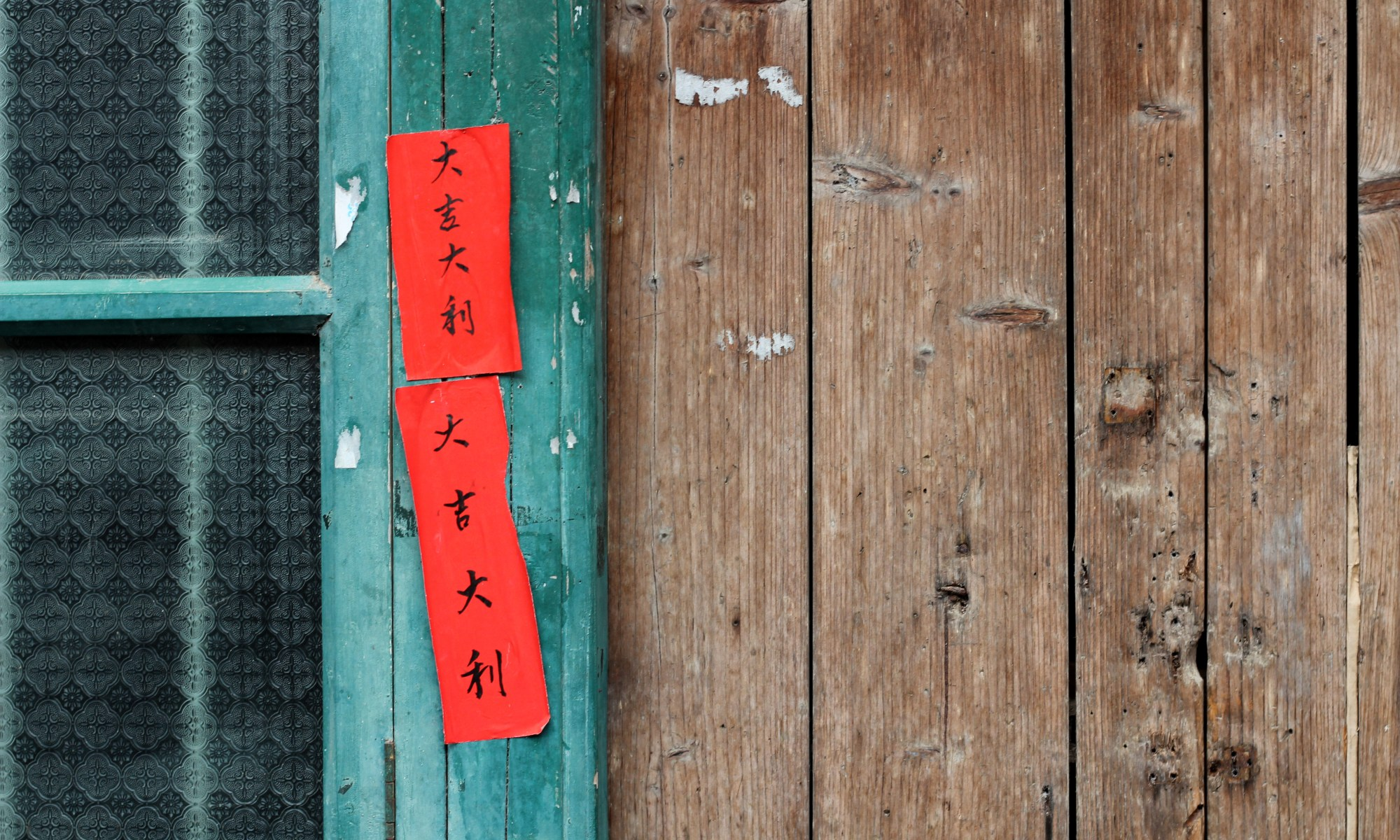 Red sign in Chinese on a turquoise door.