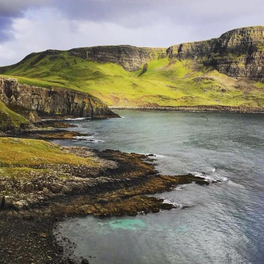 Photo of green cliffs over water lit up by sunlight