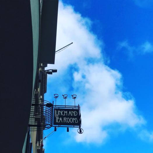 Photo of a sign that reads tea room in Makintosh style fonr
