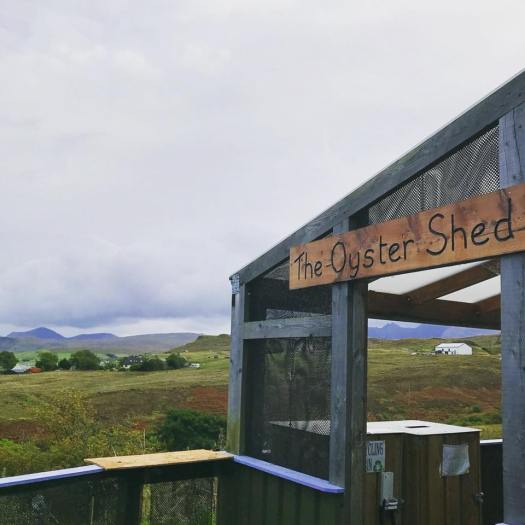 Photo of the Oyster Shed's wood sign against the backdrop of the Scottish Highlands