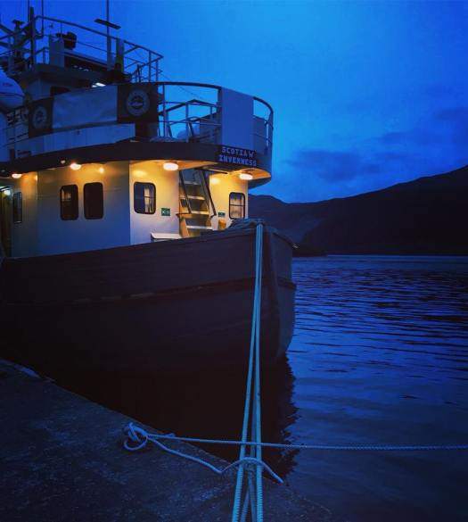 Photo of a trawler tied to a pier at night
