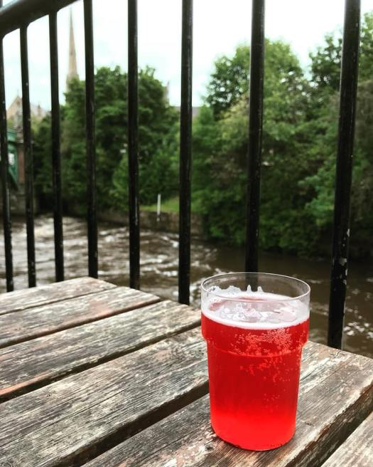 Photo of a red half pint of beer on a table by a river