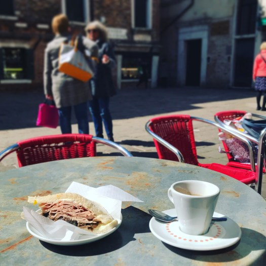 Photo of a sandwich and espresso cup on a bistro table in the sun