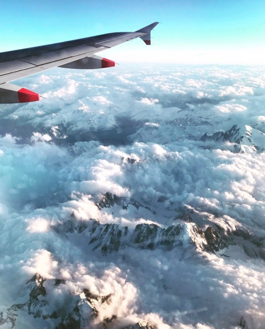 Photo of a plane wing, clouds, and mountain tops
