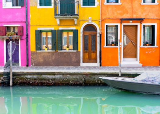 Photo of a boat outside colourful houses