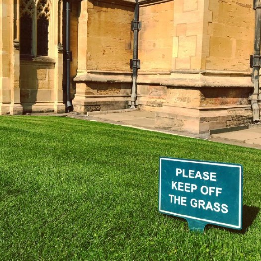 """Photo of a sign that reads """"Please keep off the grass"""""""
