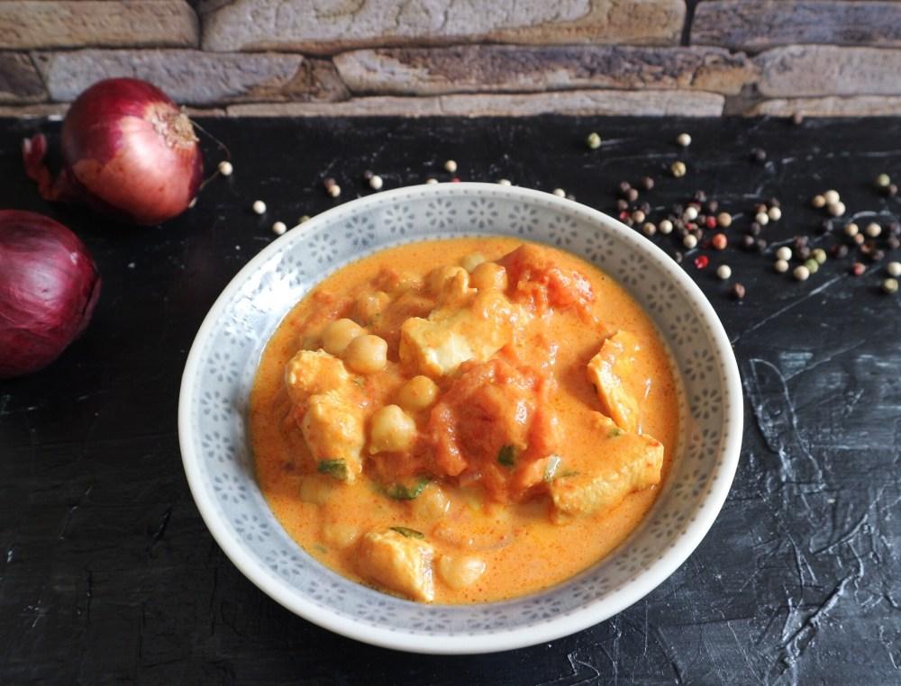 Vegetarisches Curry mit Tomaten, Kokosmilch, Grillkäse, Möhren, Süßkartoffeln und Kichererbsen.