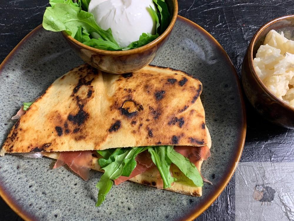 Piada mit Rucola, Schinken und Burrata. Begleitet von Blumenkohl