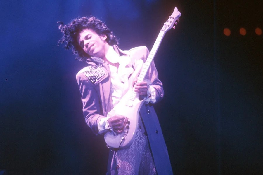 Prince playing guitar in purple light.