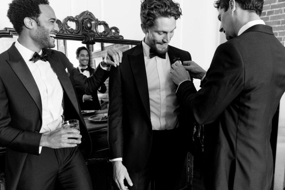 Groomsmen help groom prepare in The Black Tux tuxedos.