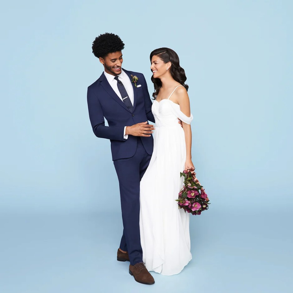Man in blue men's wedding suit with bride in gown.