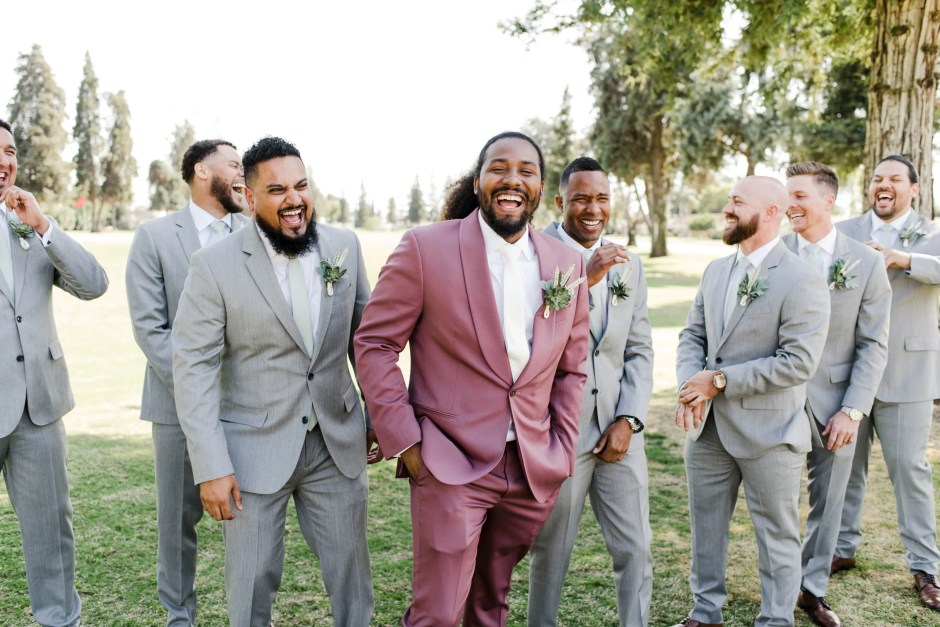 groomsmen in grey suits groom in bold rose summer wedding attire