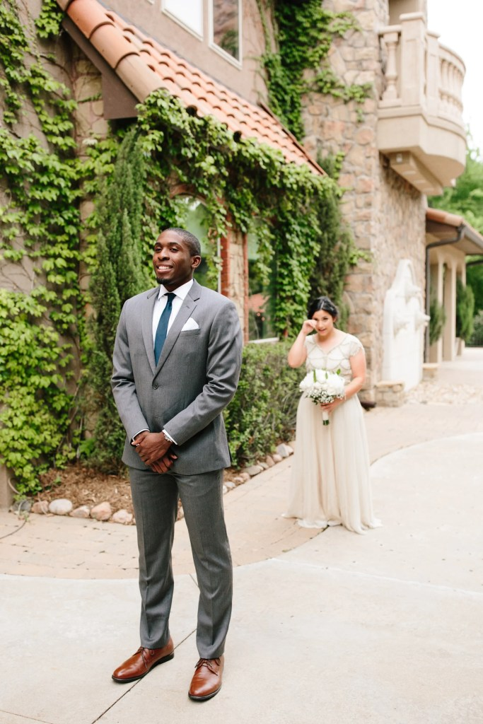 groom in grey suit summer wedding attire with brown shoes bride in background