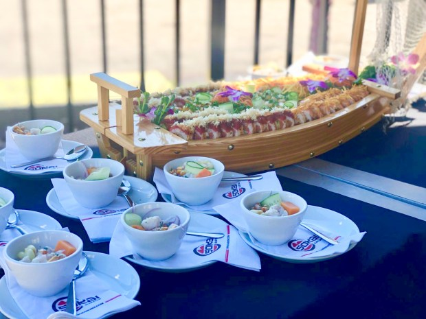 Small bowls of ceviche and a sushi boat on top of a table