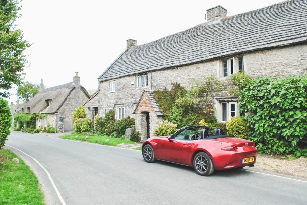 Corfe Castle English countryside village with red Mazda MX 5 Jurassic Coast Dorset