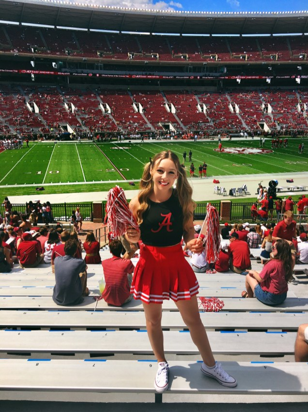 Cheering on the Alabama Crimson Tide at a school football game.