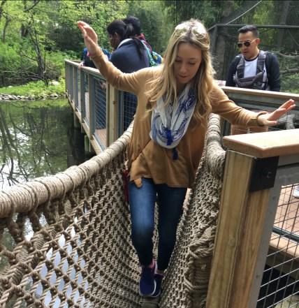 Balancing across the rope bridge.