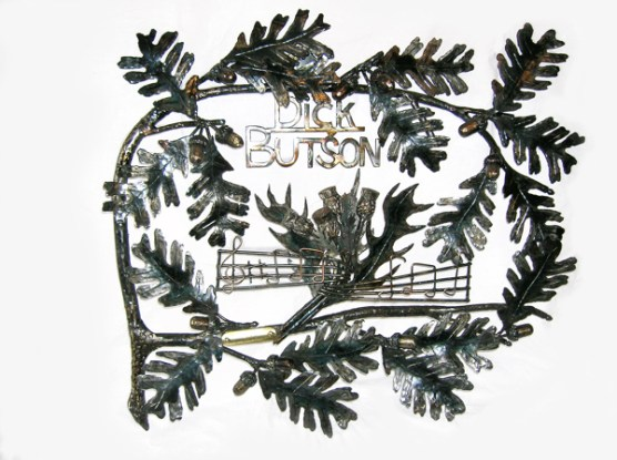Picture of steel sculpture made of oak leaves surrounding a name and sculpted scottish thistles, by Jim Davis.