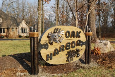 Photograph of sign saying Oak Harbor, it's made of steel letters and oak leaves on a wooden background. By Jim Davis