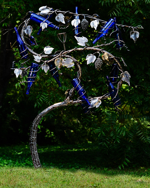 Picture of sculpted metal grapevine and grapes displayed with blue wine bottles by Jim Davis.