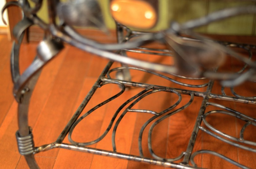 Closeup detail photography of shelf of wrought steel table, with the name Val incorporated into the design. By Jim Davis