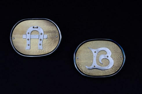 picture of brass and steel belt buckles with the letters A and B.